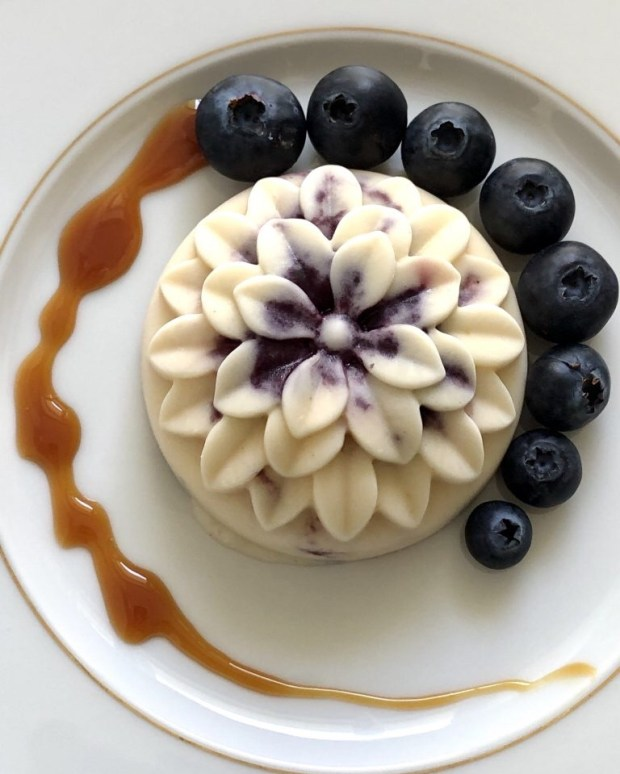 Ein Eis in Dahlienform mit Heidrlbeeren und Karamell-Sauce auf cremefarbenem Teller mit Goldrand