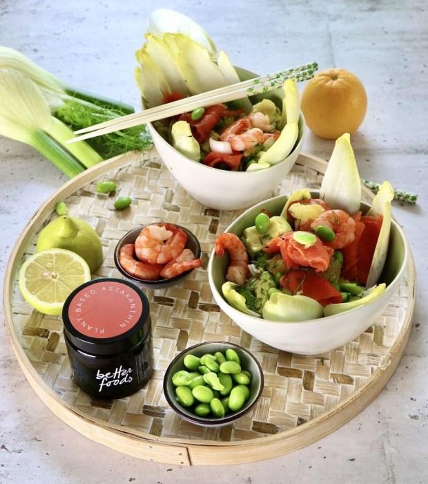Zwei Schüsseln mit Fenchel-Salat mit Lachs auf Bambus-Tablett, dekoriert mit  den Zutaten und    einer Dose Astaxanthin von Better Foods