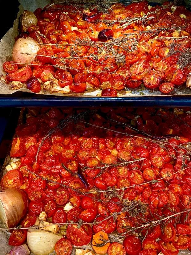 Zwei Backbleche mit Tomaten und anderen Zutaten für die geröstete Tomatensauce im Backofen