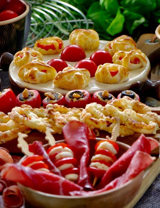 Snackboard mit gefüllten Tomaten, Blätterteig-Brezeln , Oliven, Nüssen, Salami, Bresaola