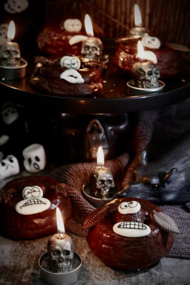 Grumpy Donuts vor dunklem Hintergrund mit Totenkopf-Teelichtern dekoriert.