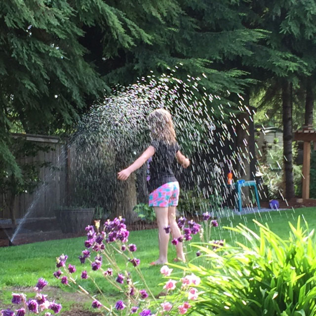 Girl in sprinkler, landscaping