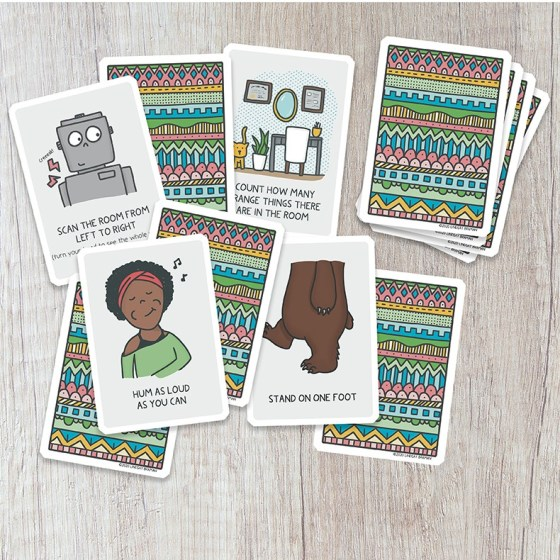 Assortment of cards with illustrated ideas for mindful grounding, shown next to a colorful deck and text