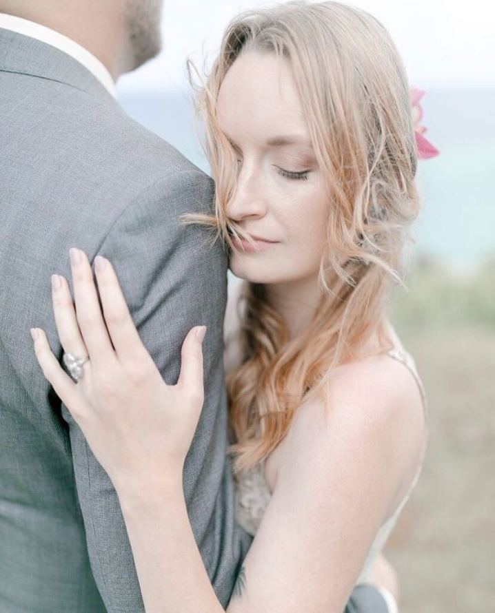 Chelsea Horton with her left arm holding her husband and her eyes closed