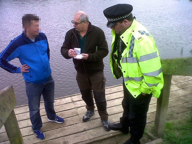 Thames Valley Police Wildlife Crime Officer Ian Whitlock, right, looks on as Environment Agency Fisheries Enforcement Officer Mick Cox reports an angler for fishing without a rod licence on the Thames. These joint patrols emphasise that the police and Agency are sharing intelligence and increasingly mounting joint patrols on our waterways.