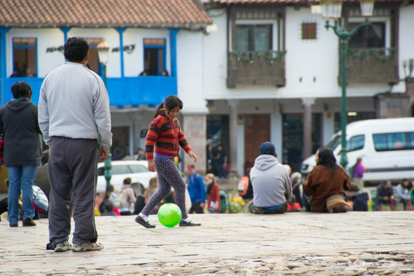 Father and daughter kicking a ball around in Plaza de Armas