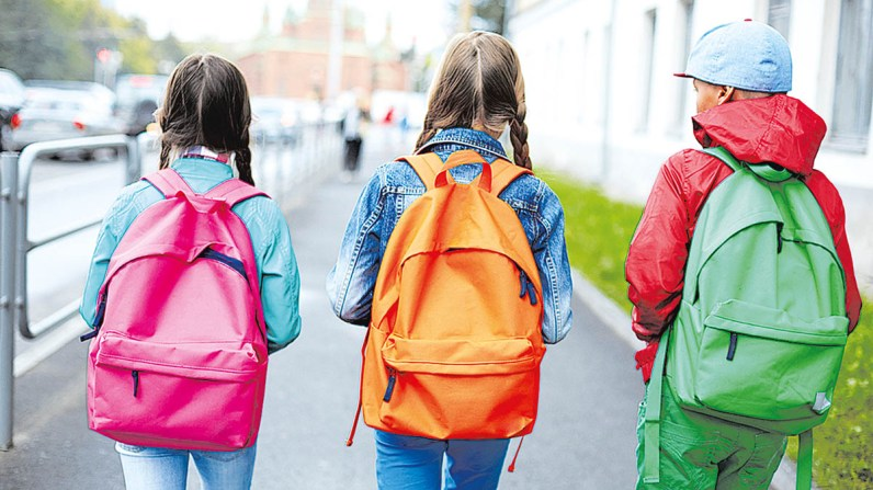 Backs of schoolkids with colorful rucksacks moving in the street; Shutterstock ID 219008878; PO: TODAY.com