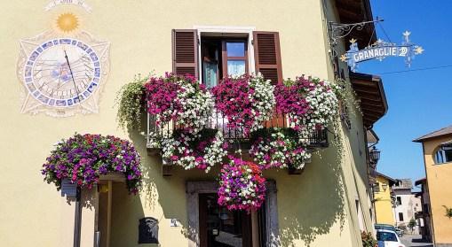 Hausfassade mit Sonnenuhr und Blumenkästen