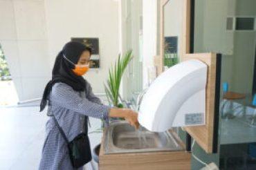 Foto perempuan sedang mencuci tangan sebelum memasuki gedung [Doc. BP2M]