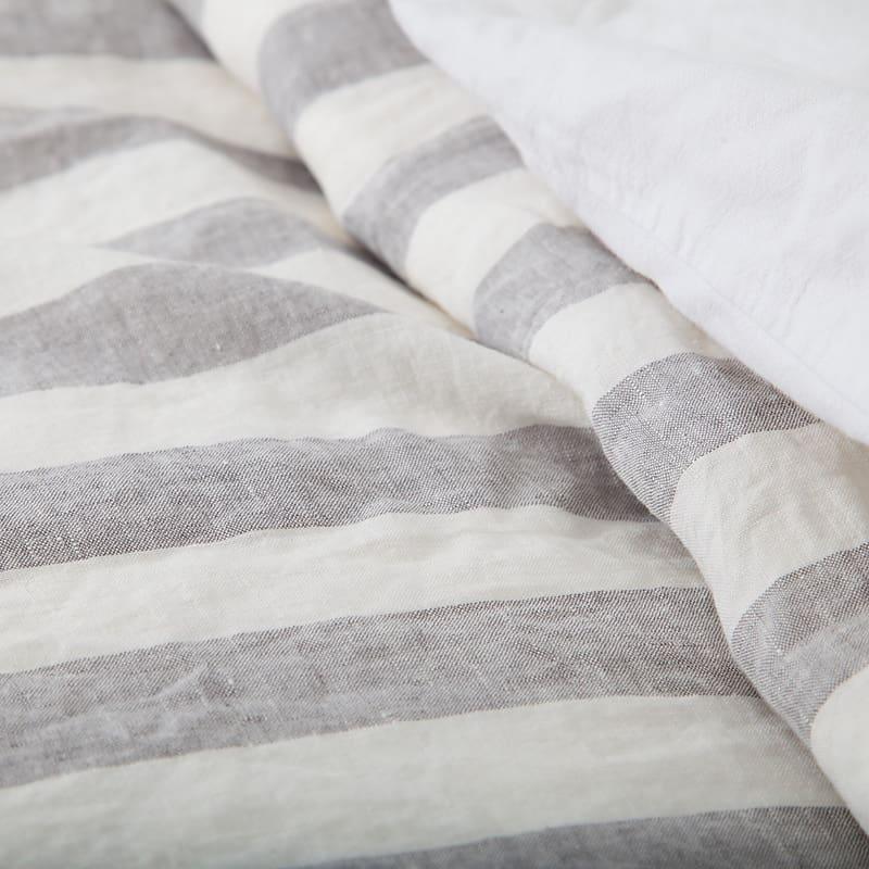 detail van linnen dekbedovertrek in grijs met witte steep