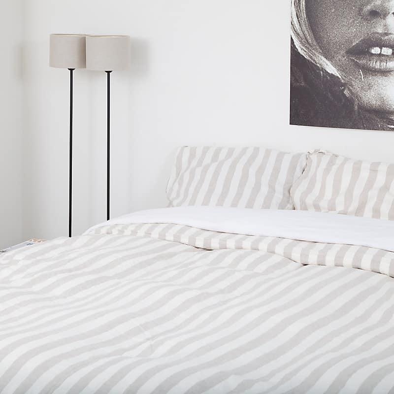 Moderne slaapkamer met witte muren en een linnen dekbedovertrek met verticale beige met witte strepen.