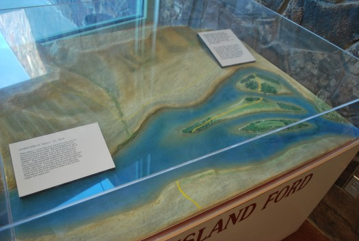 A display showing an aerial view of Three Island Crossing