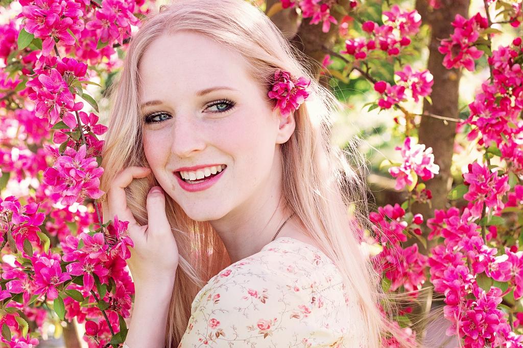 Informationen über mich. Blondes lachendes Mädchen mit Blumen im Hintergrund