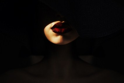 Woman-with-a-black-hat-and-red-lip-in-a-shadow youqueen dot com
