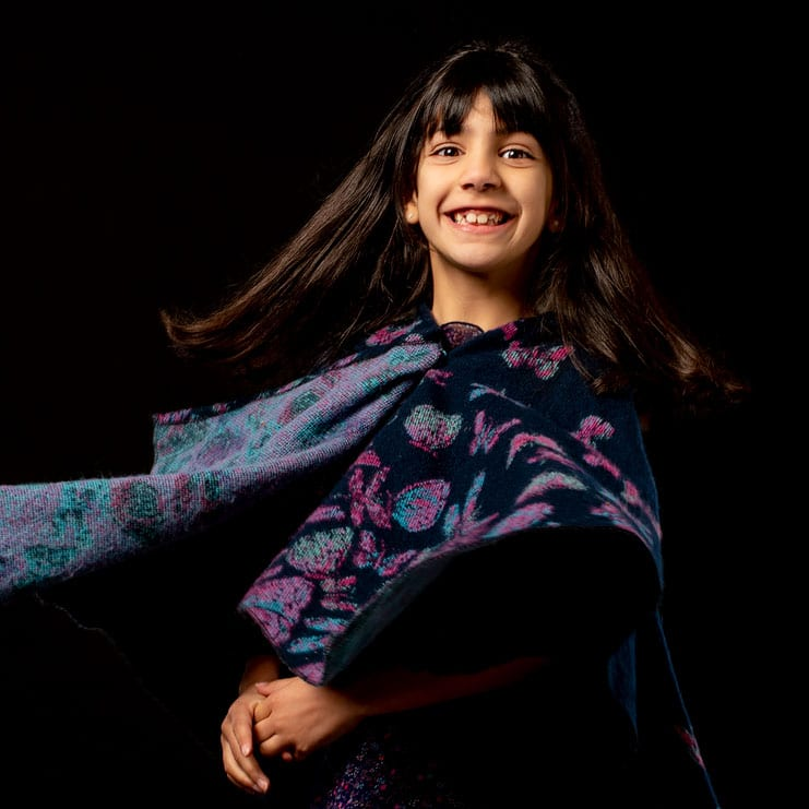 portrait of child spinning in poncho