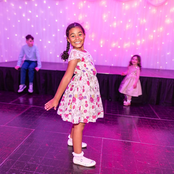 girl poses on dance floor at wedding reception