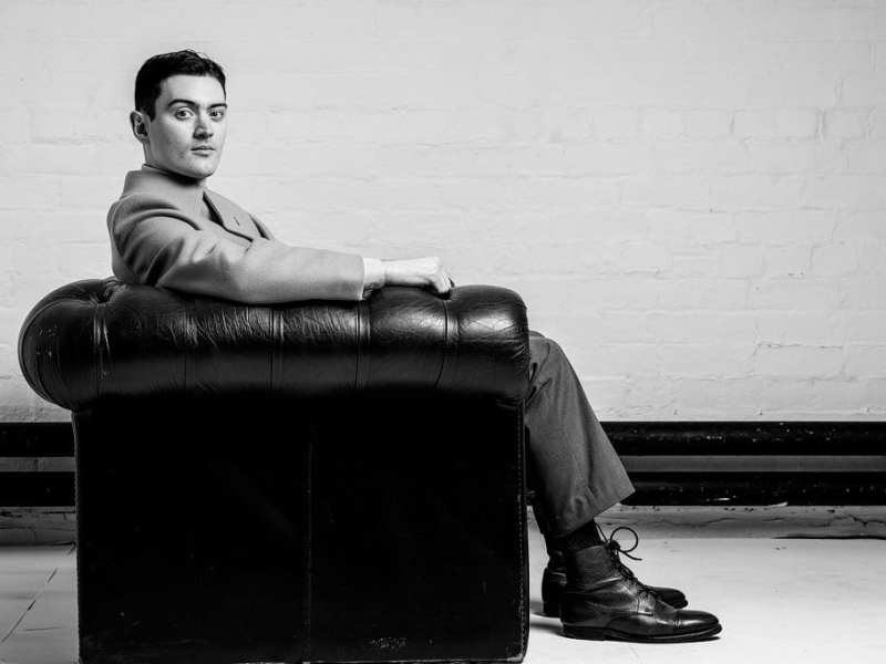 An actor poses on a couch in classic suit.