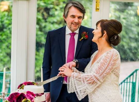 the bride and groom share a loving look as they cut their wedding cake