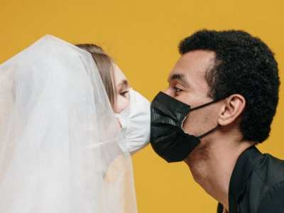 man in black suit kissing woman in white veil