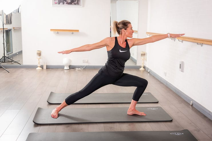 pilates student in nike top strikes a pose