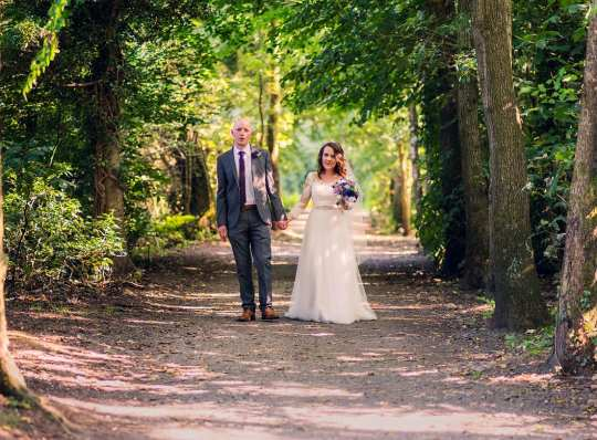 Bride and Groom walk in forest