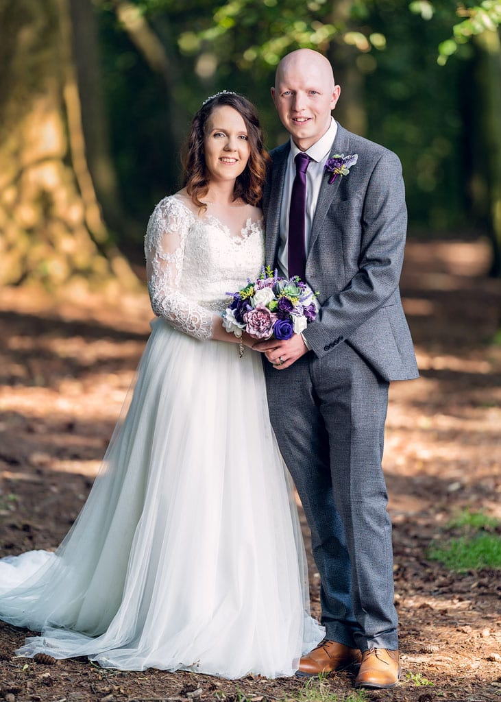 bride and groom pose in forest