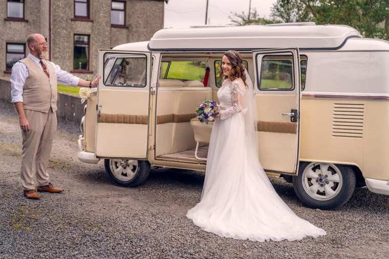 bride poses by vw camper van wedding car