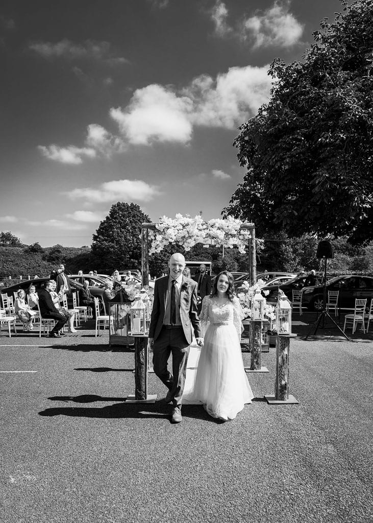 bride and groom walking down outdoor aisle on sunny day