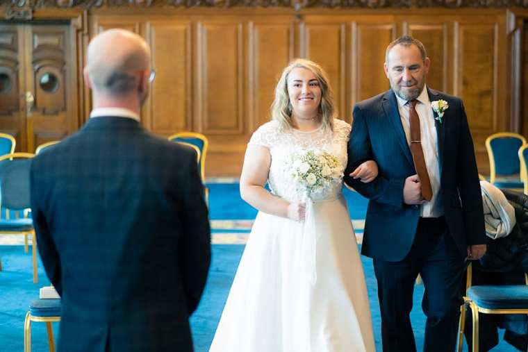 bride arrives at alter escorted by her father