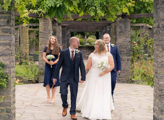 a most relaxed couple walk under a pergola on their wedding day