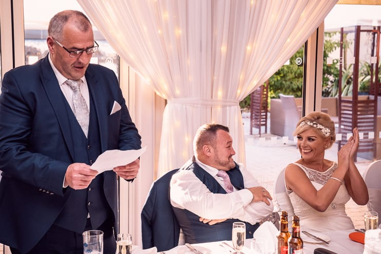 the bride and groom share a moment as the best man makes his speech