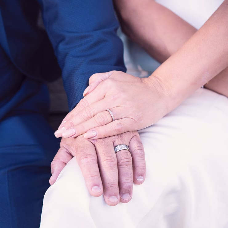 the hands of the bride and groom with wedding rings