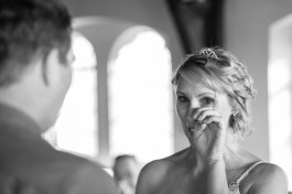bride tearing up in a church while listening to vows