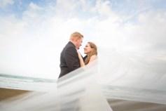 bride and groom veil flowing blue skies