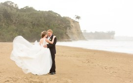 auckland wedding bride and groom embracing on beach