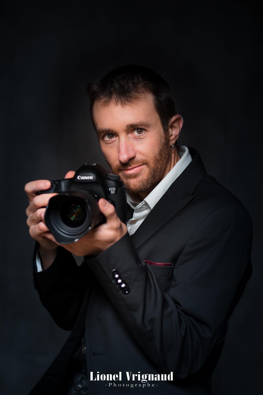 Le photographe se tient avec son appareil photo pour un autoportrait