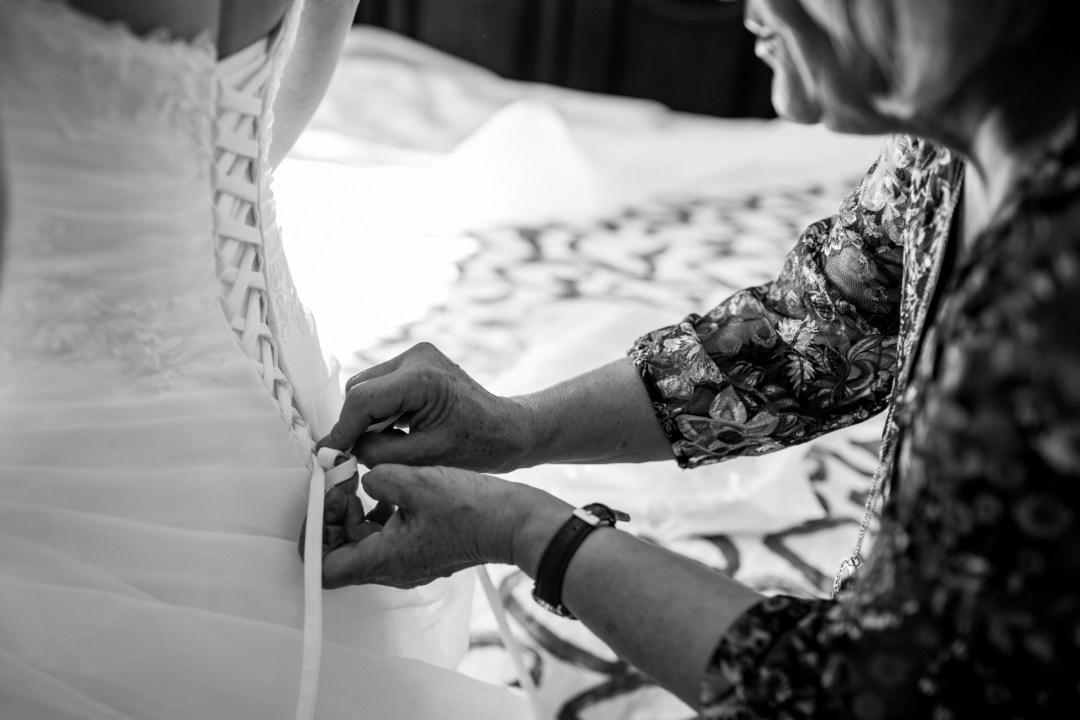 La maman de la mariée l'aide à préparer sa robe pour leur mariage à la Roche sur Yon