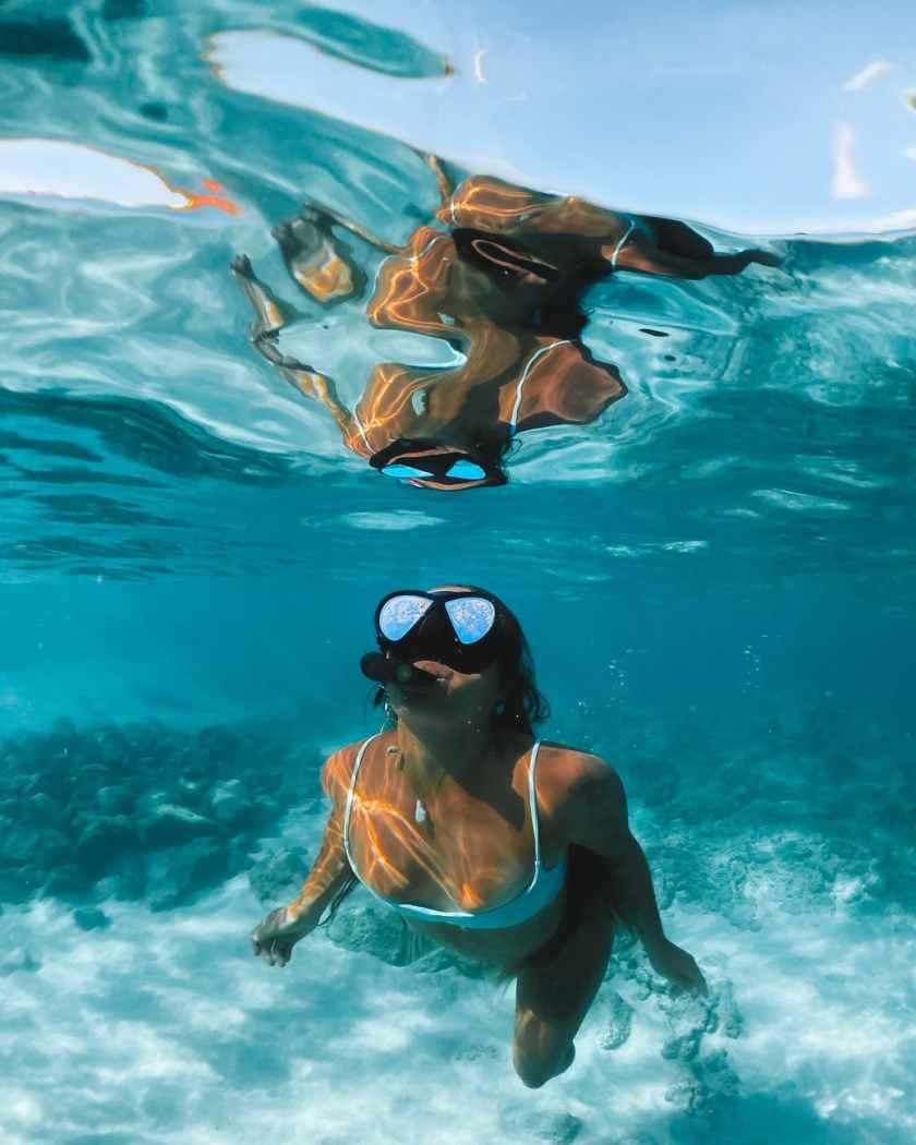 woman in black sunglasses and brown bikini top in water