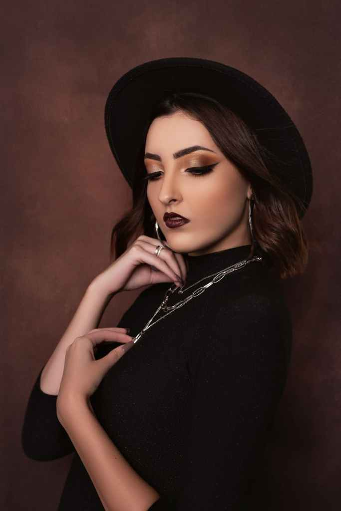 stylish female in black hat against brown background