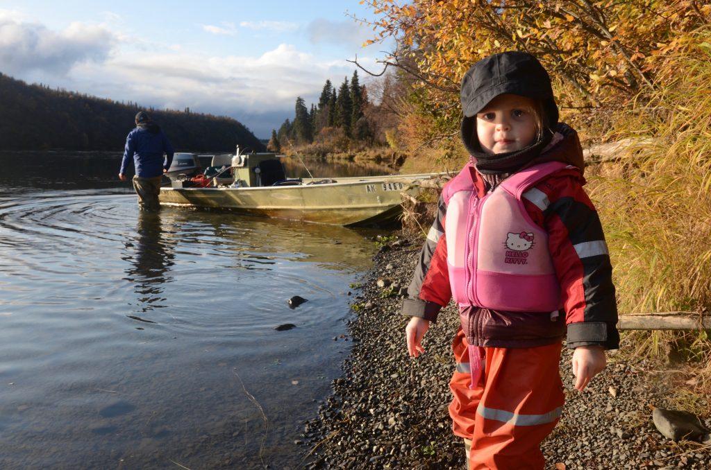 Little girl fishing on lake shore