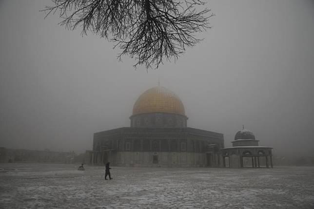Seorang pria berjalan di dekat Masjid Kubah Batu di kompleks Masjid Al Aqsa pada pagi bersalju di Kota Tua Yerusalem, Kamis (18/2).