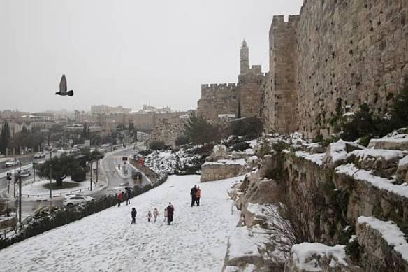 Orang-orang berjalan di salju di taman di samping tembok Kota Tua Yerusalem, Kamis (18/2).