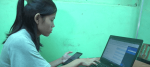 Photograph of a female freelance translator working on a laptop with a phone in her hand