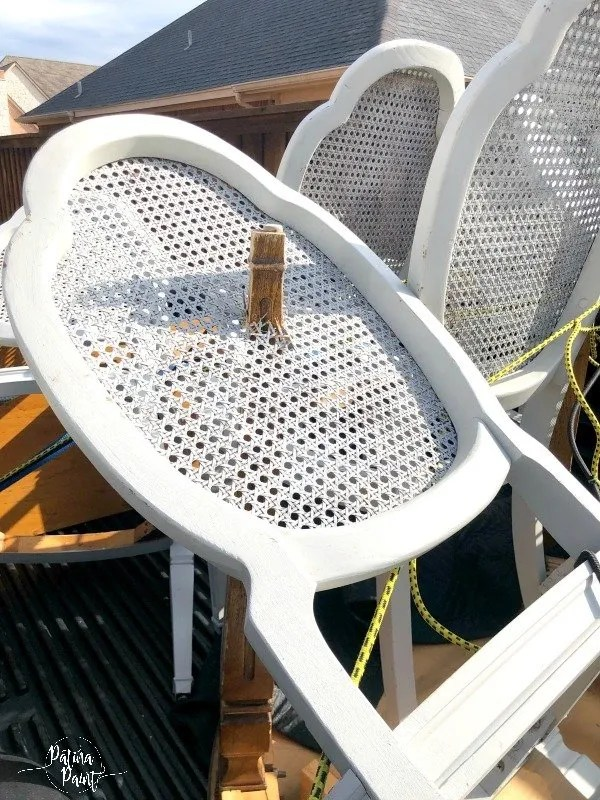 cane back chair with table leg through it