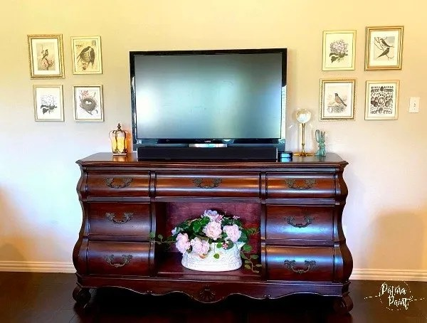 tv, tv console, pictures on wall