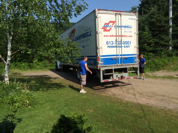 Two of the crew helping to direct the truck while backing up the driveway.