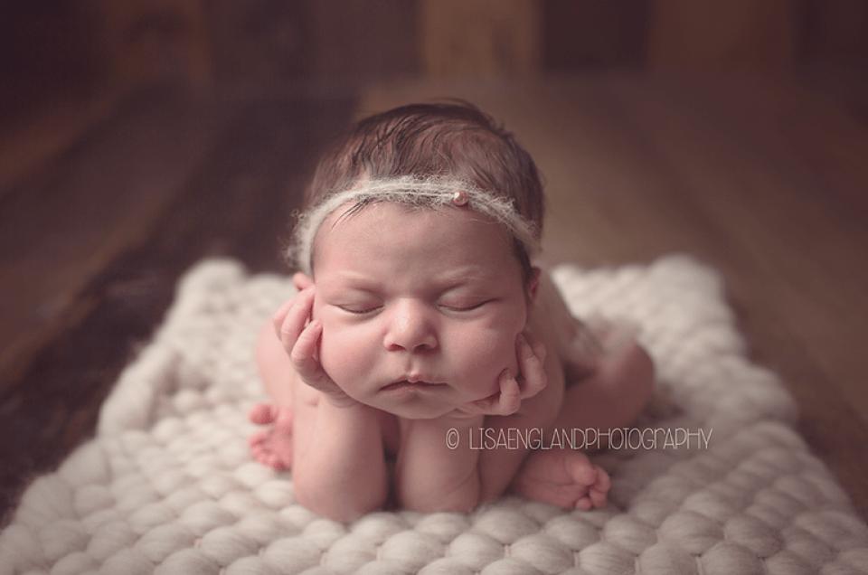 cute newborn with chin in hands