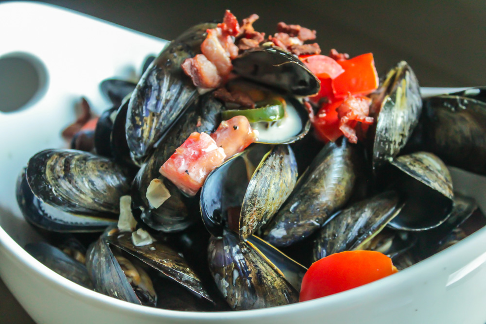 Spicy Mussels in a White Wine Cream Sauce with Bacon and Tomatoes
