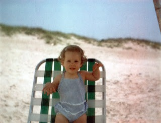 young girl in blue and white checked swimsuit standing on beach chair at the beach