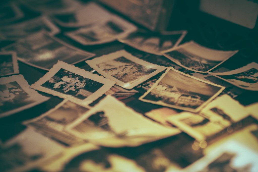 Scatter old family photographs in black and white with white borders